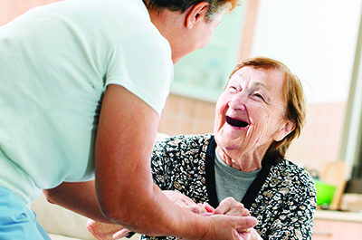 Woman Laughs With Caregiver
